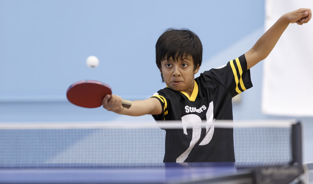 Cary 8-year-old Anva Guptakeeps his eyes on the ball while playing his father, Arvind, at the Triangle Table Tennis Center in Morrisville.