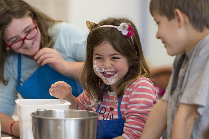 Alena Dabrowski, center, figures out the hard way that powdered sugar can get everywhere if you aren't careful. Kyra Pettibone, 10, left, and Alex Earl find the spectacle just as amusing as Alena does.