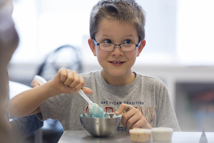 """Andrew Earl, 8, likes to cook eggs and bacon at home, but doesn't like to share the kitchen with his brother, Alex. He enjoyed the day of baking, especially the morning project — apple fritters. """"They were delicious,"""" he said."""