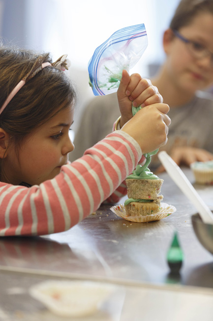 """Alena Dabrowski squeezes green-tinted vanilla buttercream icing onto her cupcake during a one-day workshop at Flour Power Kids Cooking Studio in Cary. The 7-year-old cooks a lot with her mom back home in Australia, but she says she learned a few things during her visit to North Carolina. """"I liked tasting new things that aren't  popular in Australia. I tried stromboli; it tasted really good — sweet and not sweet at the same time."""""""