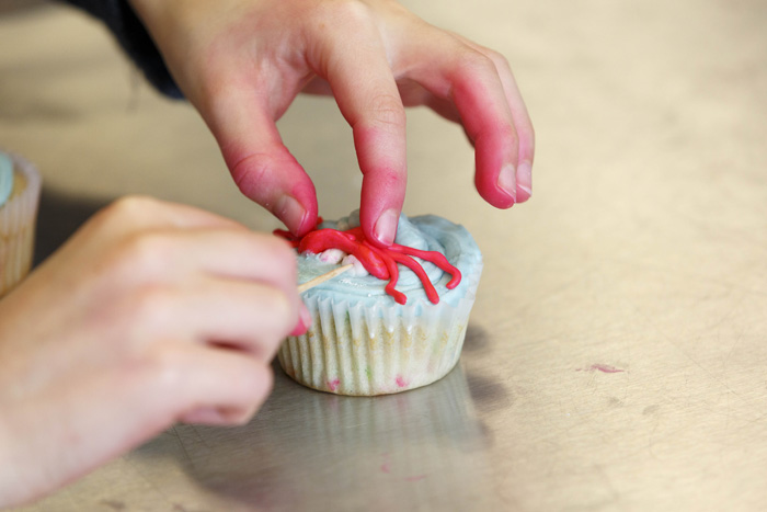 """A crab-topped cupcake gets some finishing touches during the final activity of the day-long workshop — a competition inspired by the Food Network program """"Cupcake Wars."""""""