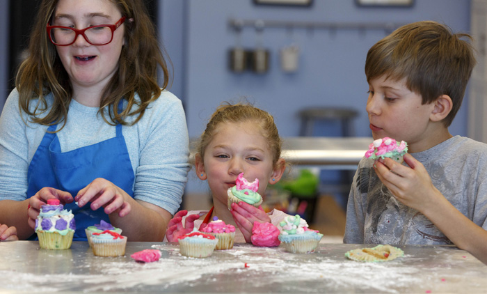 """Kyra Pettibone, left, Dylan Salzman, center, and Alex Earl dig into the cupcakes they've decorated. """"I like making cakes and cupcakes — I like icing them,"""" said Kyra, who received a set of icing tubes for her last birthday."""