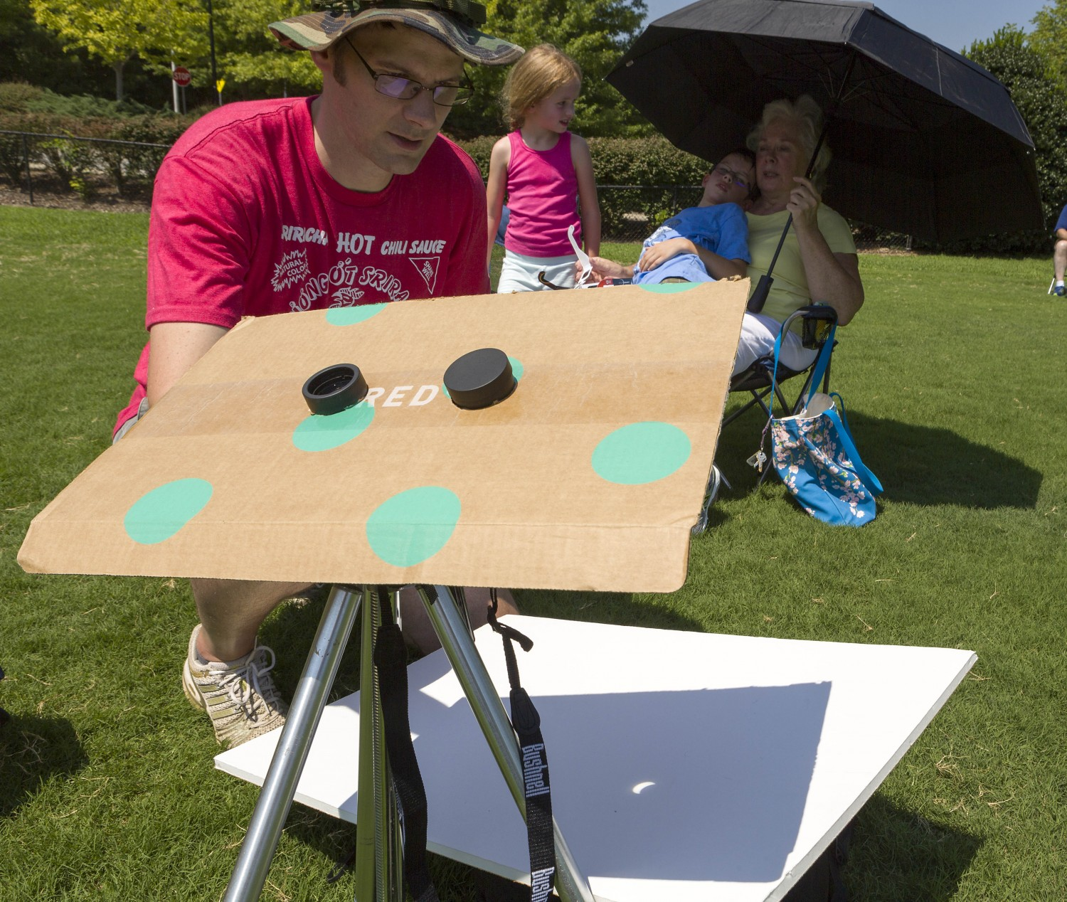 Using a pair of binoculars, T.J. Hill of Cary projects and magnifies an image of the solar eclipse on a piece of foam core. Hill tried out his pinhole camera at North Cary Park, where he and his family joined others for the historic event.